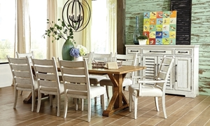 "7-piece dining room set featuring a 100"" trestle style wooden table, 4 ladderback side chairs, and 2 arm chairs in a rustic distressed chalky white finish."