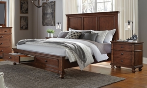 Functional king size storage bed in a warm whiskey brown finish featuring two spacious footboard drawers and hidden USB charging ports along the headboard.