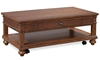 Traditional coffee table with storage drawer and casters in whiskey brown