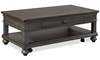 Traditional peppercorn gray coffee table with storage drawer, shelf and casters.
