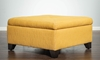32-inch square storage ottoman in gold upholstery with dark wood feet