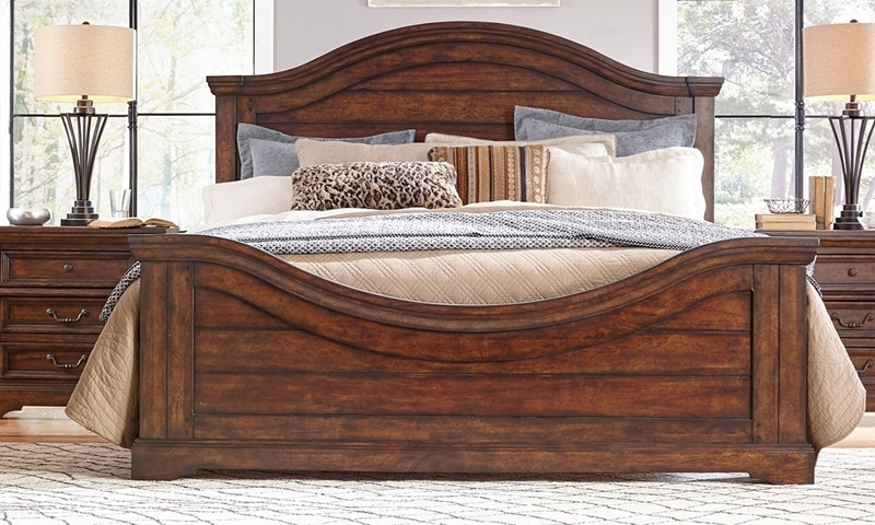 Rustic queen bed with wood plank panels and curved accents on headboard and footboard in warm tobacco brown finish