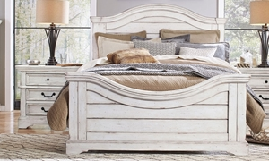Cottage inspired king panel bed with arched headboard and footboard in antique white finish