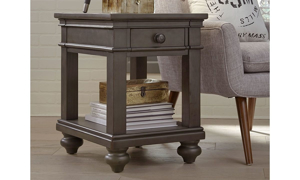 Traditional side table with drawer and lower shelf in peppercorn gray finish next to sofa in living room