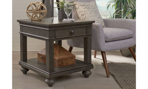 Traditional end table with lower shelf and storage drawer in peppercorn gray next to chair in living room