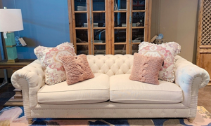 Hand-tailored roll arm chesterfield sofa with tufted detailing, feather down blend seats, & 4 decorative pillows fit for a small vintage style living room.