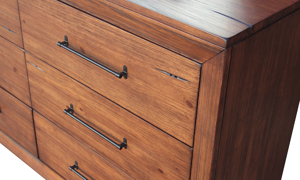 Close-up of contemporary 6-drawer solid pine dresser with metal drawer pulls in brushed brown finish