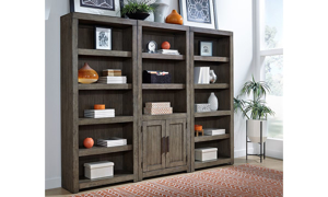 Modern 75-high triple bookcase in greystone finish used for display in living room