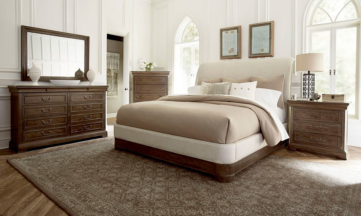 Complete bedroom set with upholstered sleigh bed in neutral tone, dresser with mirror, chest and nightstand