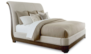 Louis Philippe style sleigh bed with neutral tone upholstered headboard