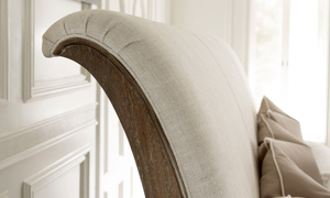 Close-up of upholstered sleigh headboard in neutral tone upholstery on A R T St. Germain Bed