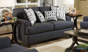Navy blue fabric loveseat with four coordinating throw pillows.