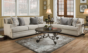 American-made couch and loveseat in a contemporary cream fabric with coordinating toss pillows.