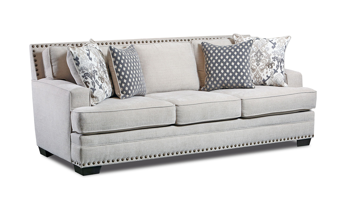 American-made fabric upholstered couch in an off-white, cream color with four throw pillows.