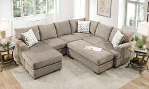 Sand-colored fabric upholstered chaise sectional with coordinating throw pillows.