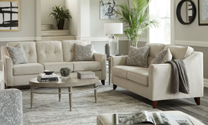 Cream-colored fabric set includes a sofa and loveseat with coordinating throw pillows.