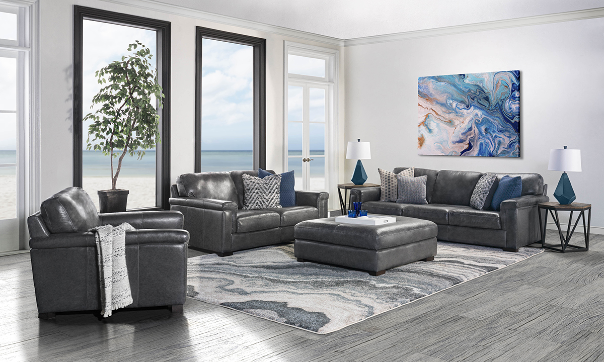 The Medici Grey Living room set includes a couch, loveseat, armchair and ottoman all made from Italian top grain leather.