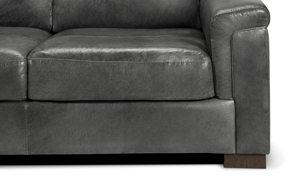 Detail shot of the leg and cushions of the Medici Grey Leather Loveseat showing the high-end tailoring, unique layover armrests and luxe grey leather upholstery.