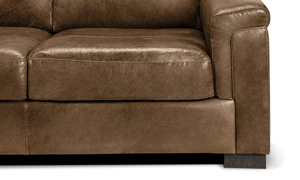 Detail shot of the leg and cushions of the Medici Chestnut Leather Loveseat showing the high-end tailoring, unique layover armrests and luxe grey leather upholstery.