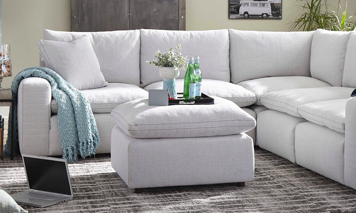 Grey fabric upholstered square ottoman.